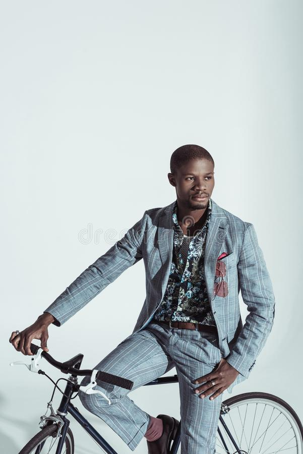 Handsome african american man in stylish suit, posing on a bike stock images