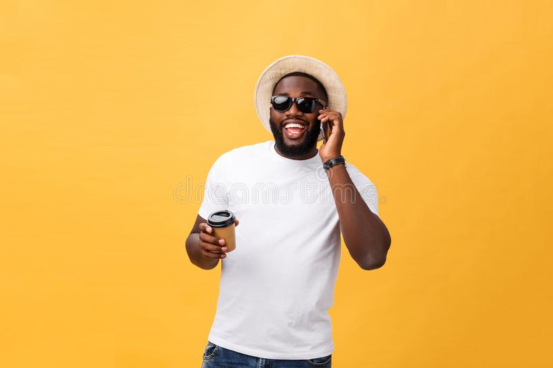 Handsome African American with mobile phone and take away coffee cup. Isolated over yellow gold background. Handsome African American with mobile phone and take royalty free stock photo
