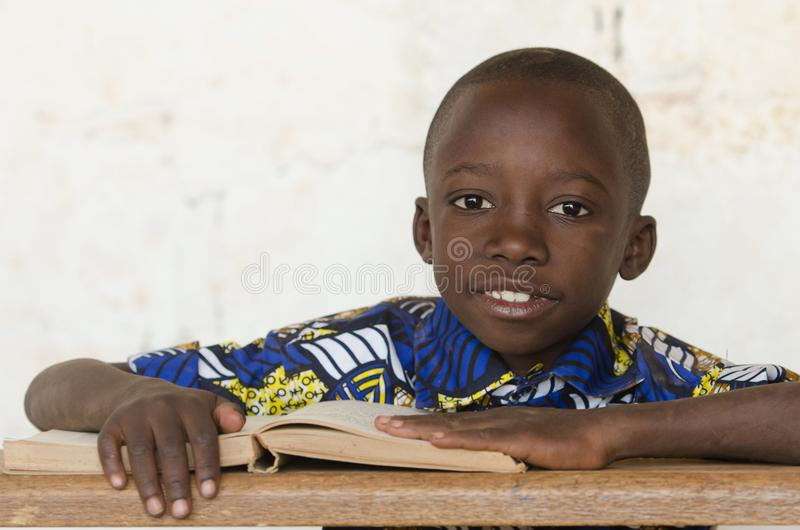 Handsome African black boy studying a Book in Bamako, Mali. Candid shot of black African children. By buying this image you support our charity projects in royalty free stock photography