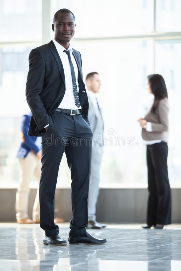 Handsome african businessman with group of businesspeople on background. stock photo