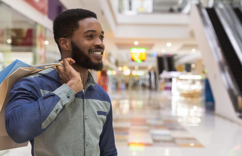 Handsome african guy with paper bags happy after shopping stock images