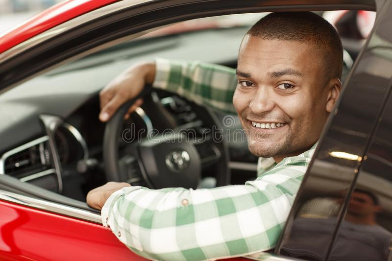 Handsome African man choosing new car at dealership. Handsome African male driver smiling to the camera, while sitting in his new car. Happy man enjoying driving royalty free stock photo