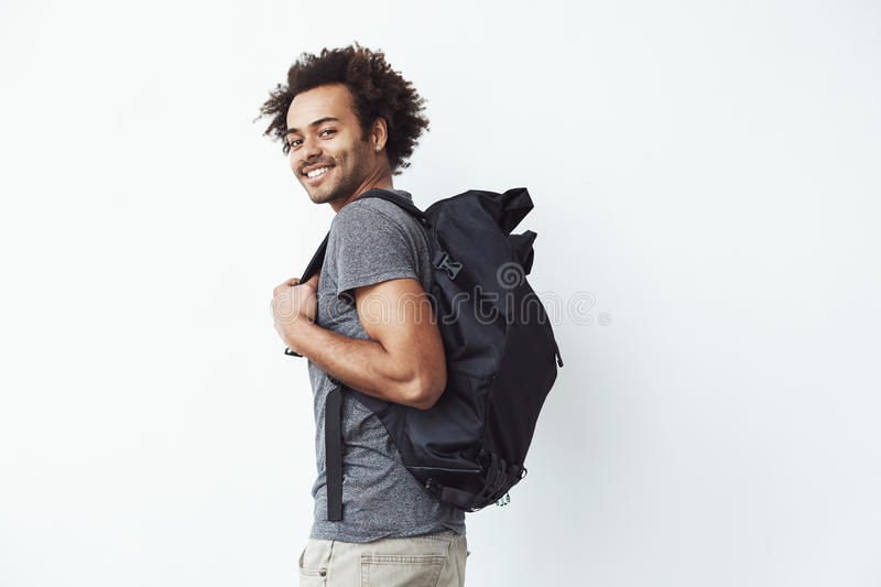 Handsome african man with backpack smiling standing against white wall ready to go hiking or a student on his way to royalty free stock image