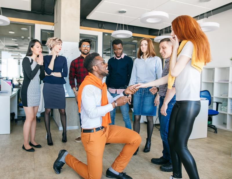 Handsome African man downing on bended knee and proposing marriage to woman. Handsome African men downing on bended knee and proposing marriage to a beautiful royalty free stock image