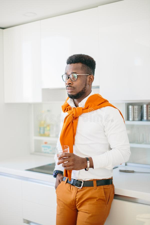 Handsome African man in glasses standing with glass of water royalty free stock photography