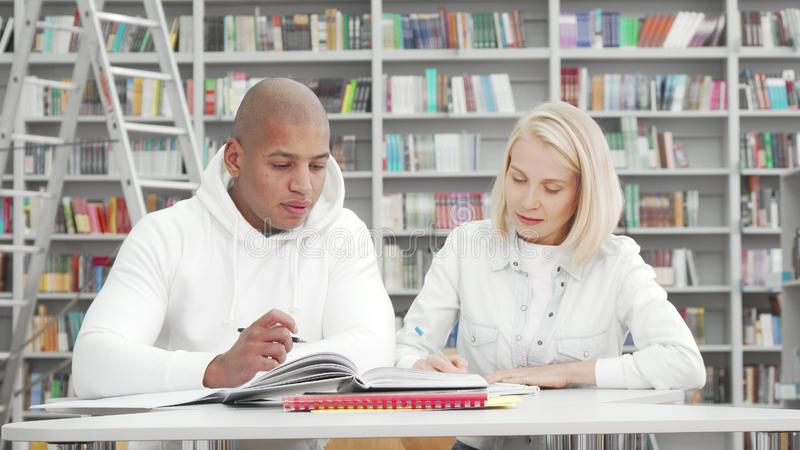 Handsome African man and his girlfriend working on college assignment together stock images