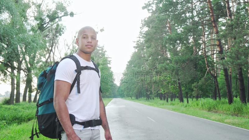 Handsome African man hitchiking on countryside road with backpack. Handsome African man hitchhiking on countryside road with backpack. Attractive cheerful male royalty free stock image