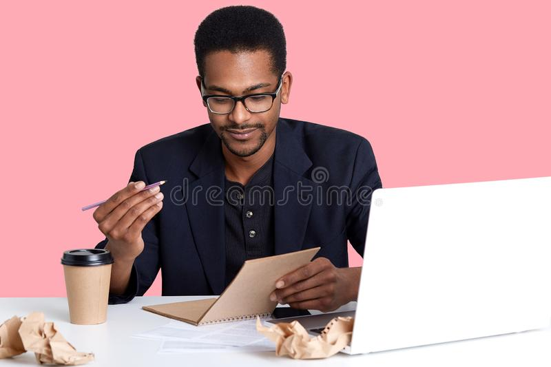 Handsome Afro American businessman in jacket and eyeglasses uses laptop. Black man holds pen and notebook in hands, wants to write royalty free stock images