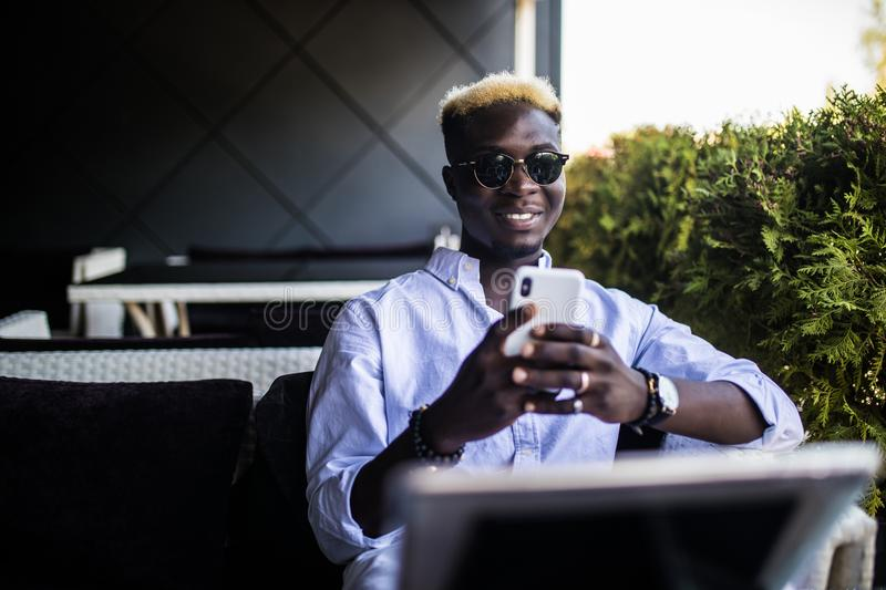 Handsome Afro American college student with cute smile typing text message on electronic gadget, sitting at cafe table with textbo stock photography