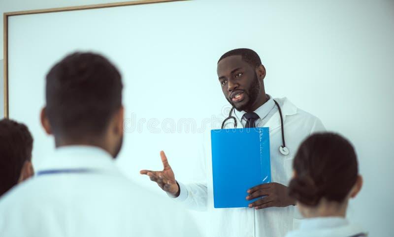 Handsome Afro American doctor die conferentierapport opstelt stock foto's