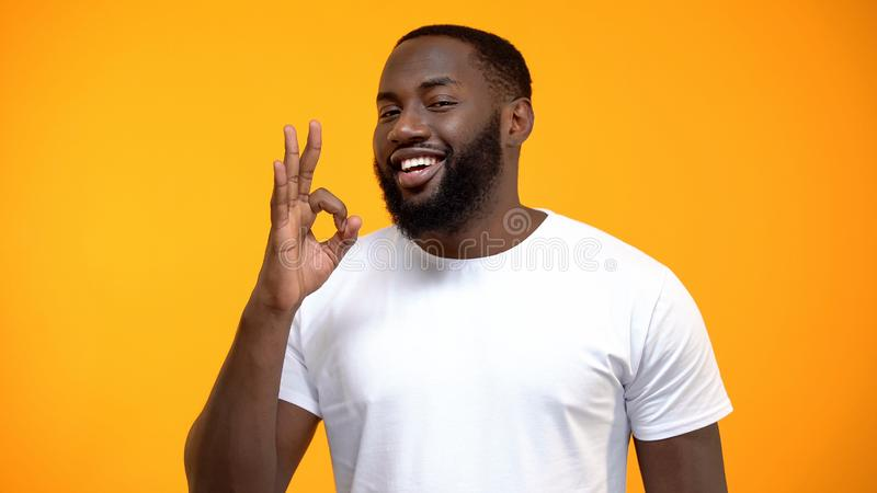 Handsome Afro-American man showing OK sign, customer review, friendly service. Stock photo stock photos