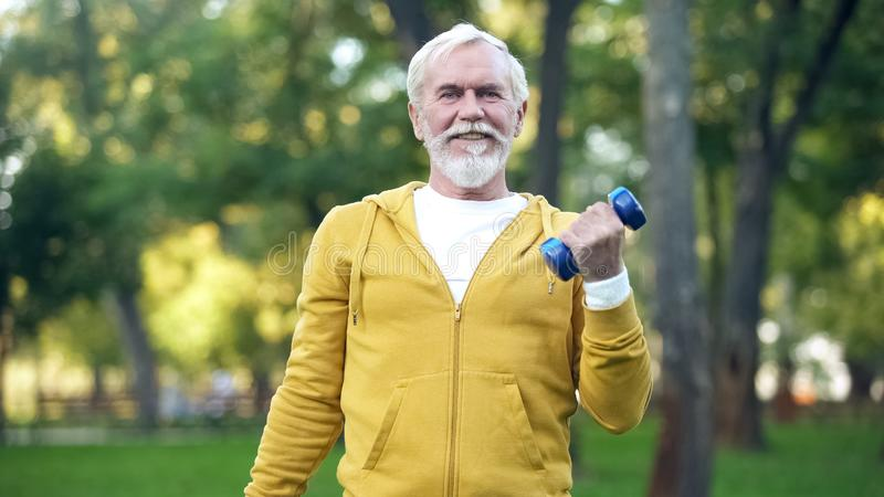 Handsome aged man doing arm exercises with dumbbells in park, leisure activity royalty free stock photos