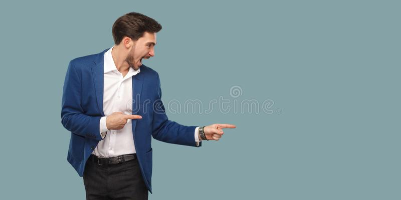 Handsome amazed bearded man in blue suit standing and pointing a stock photos
