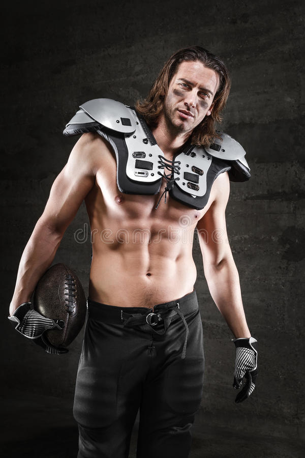 Handsome american football player. Handsome bare chested american football player royalty free stock photos