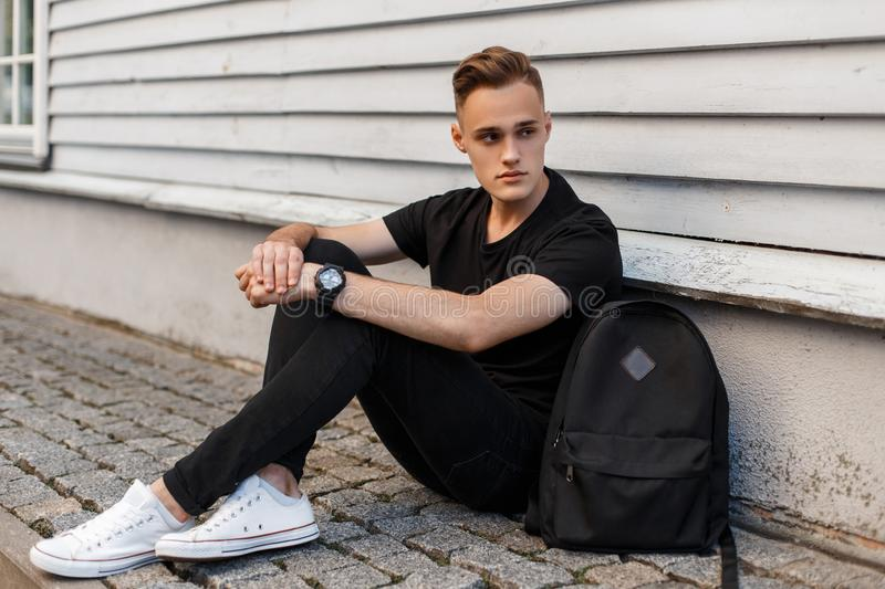 Handsome American man with a stylish hairstyle in a fashionable black T-shirt in stylish jeans in white sneakers with a backpack royalty free stock images
