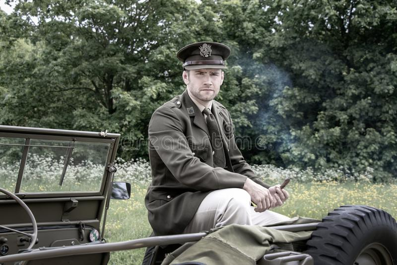 Handsome American WWII GI Army officer in uniform smoking cigar while sitting on Willy Jeep stock photo