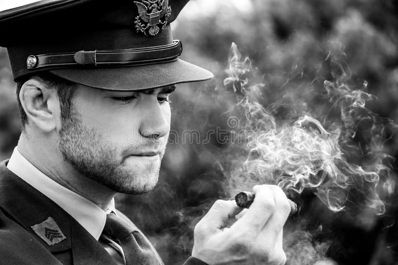 Handsome American WWII GI Army officer in uniform smoking cigar stock image