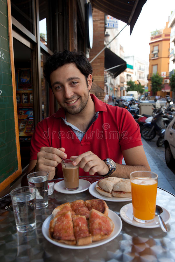 Handsome Andalusian young man having breakfast royalty free stock photography