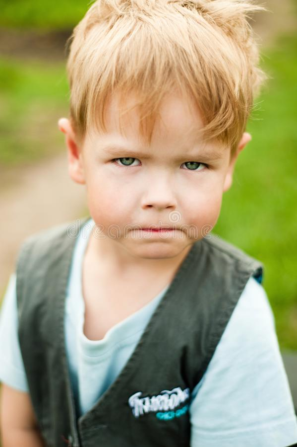 A handsome angry boy is looking at you. stock photo