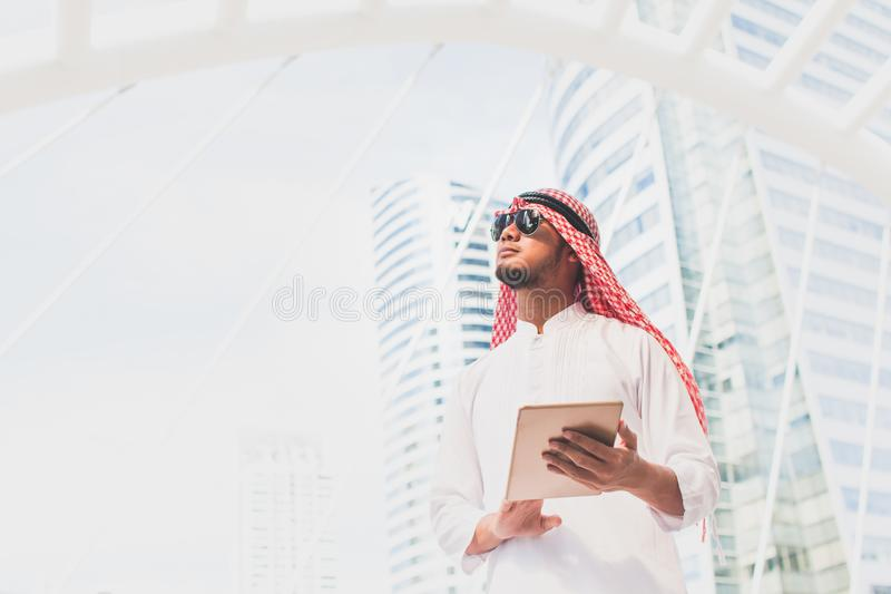 Handsome arab business man hold the digital tablet and looking to left side. Arab business man standing outside office. Finishing up a meeting, Connection stock images