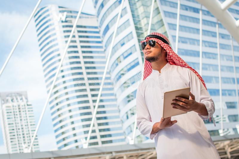 Handsome arab business man hold the digital tablet and looking to left side. Arab business man standing outside office. stock image