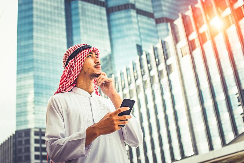 Handsome arab business man hold smartphone and looking to right side. Arab business man standing outside office. Finishing up a meeting, Connection concept stock image