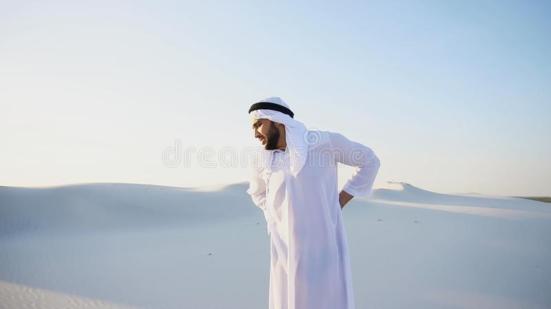 Handsome Arab sheik suffers from discomfort in back, standing in. Frustrated fellow emirate suffers from back pain and holds on to waist, feels heaviness and royalty free stock image