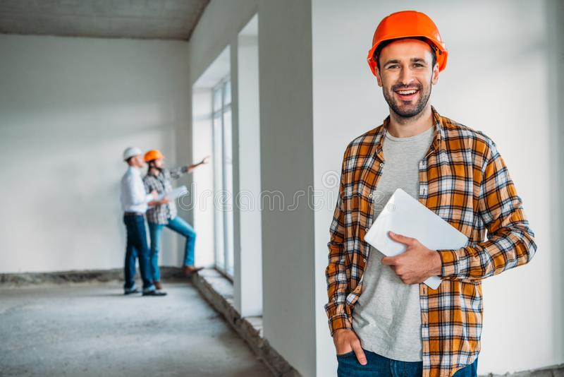 handsome architect in plaid shirt and hard hat standing inside of building house with tablet stock photography