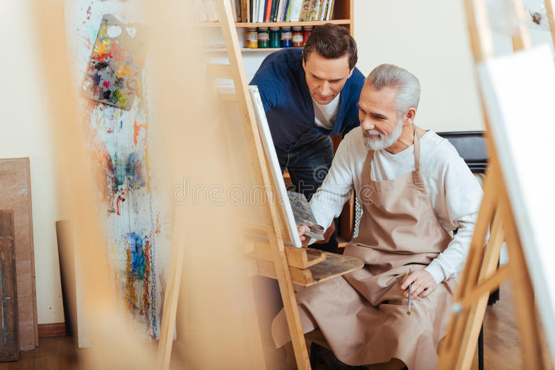 Handsome artist helping elderly man in painting royalty free stock image