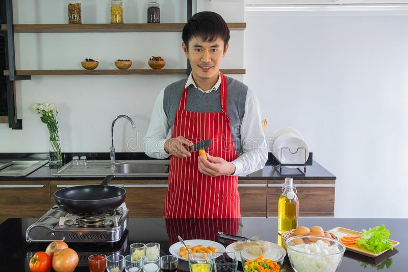Handsome, Asain young man Smiling happiness to prepare food in the kitchen. Handsome, Asain young man Smiling happiness.  Are using a slit knife at the sausage royalty free stock photos