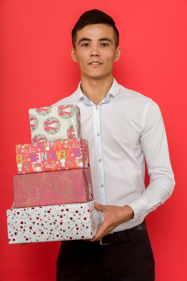 Handsome asian businessman holding gift box over red background stock photos