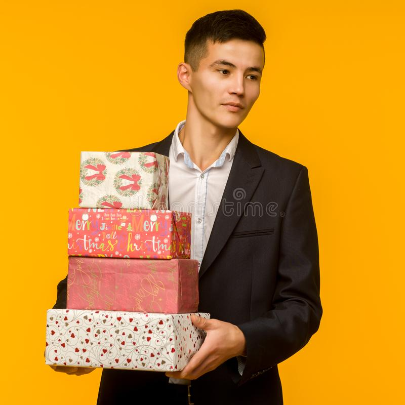 Handsome asian businessman holding gift box over yellow background stock image