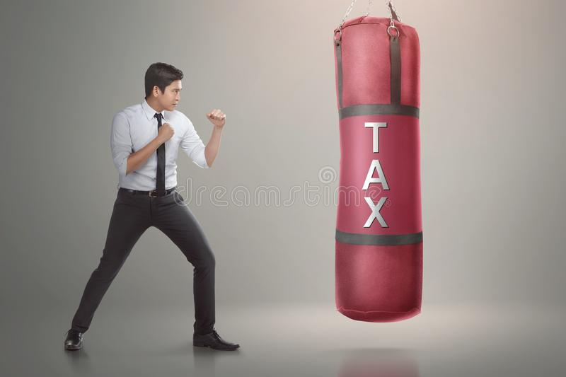 Handsome asian businessman ready to punch boxing bag with tax te. Xt on it. Taxation concept royalty free stock photo