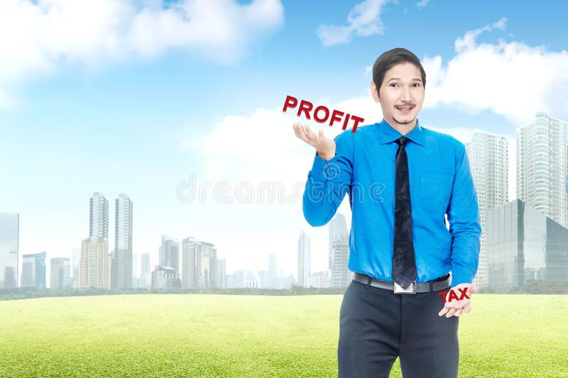 Handsome asian businessman showing unbalanced between profit and tax. Taxes concept royalty free stock photography
