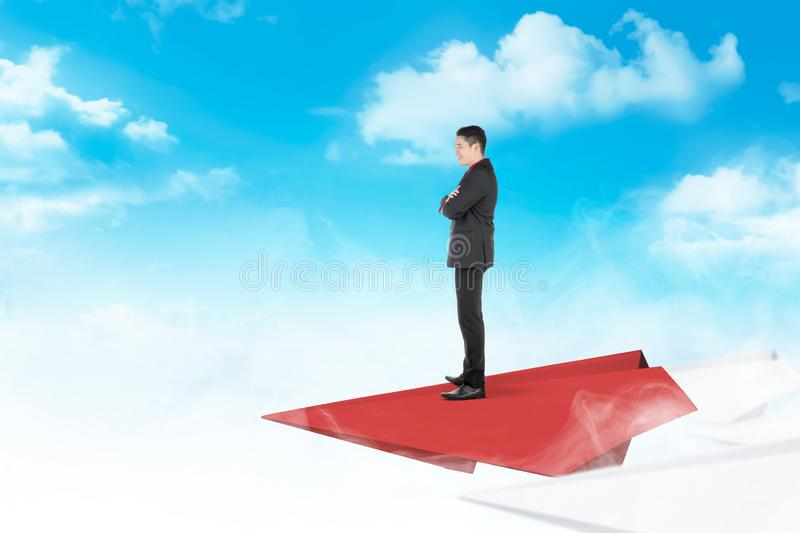 Handsome asian businessman standing on paper plane flying stock photos