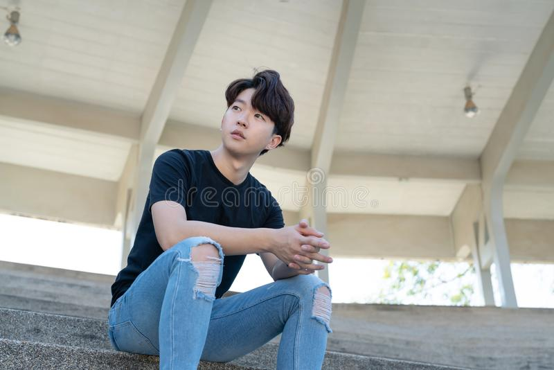 Handsome asian CASUAL man sit on a staircase posing on grandstand background. Portrait of young KOREAN against staircase background stock images