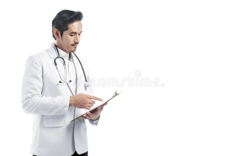 Handsome asian doctor man wearing lab coat reading notes on the royalty free stock image
