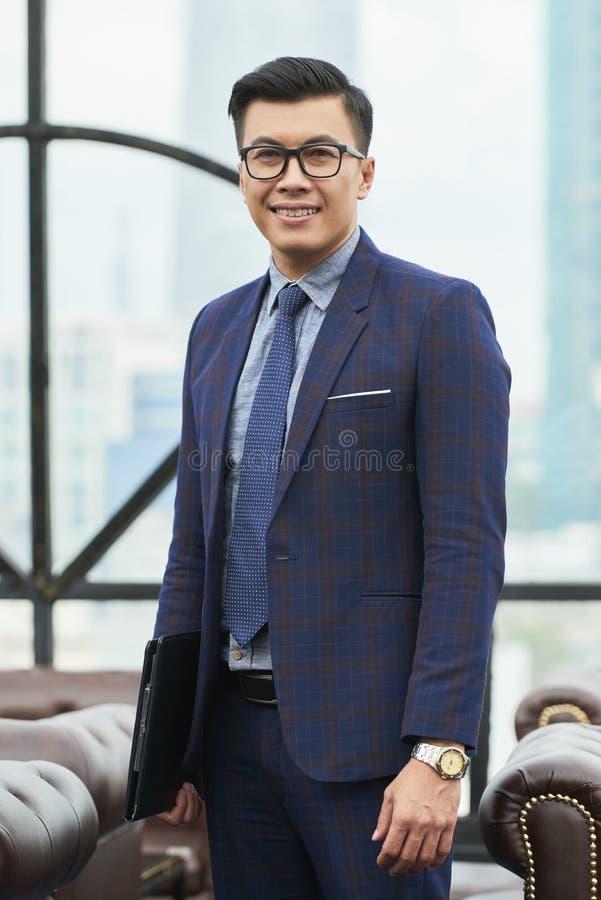 Handsome Asian entrepreneur. Positive handsome Asian entrepreneur with documents folder royalty free stock image