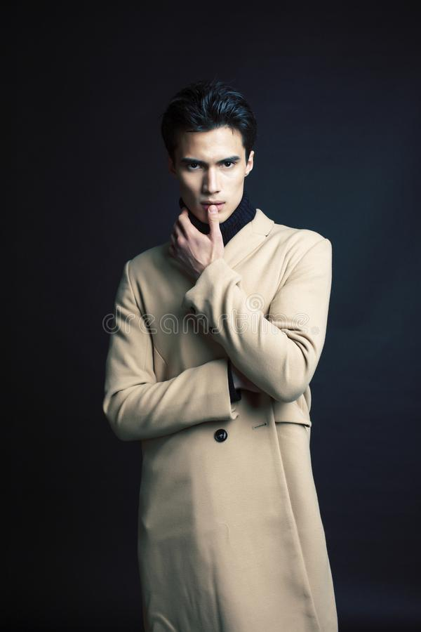 Handsome asian fashion looking man posing in studio on black background, lifestyle modern people concept close up royalty free stock photography