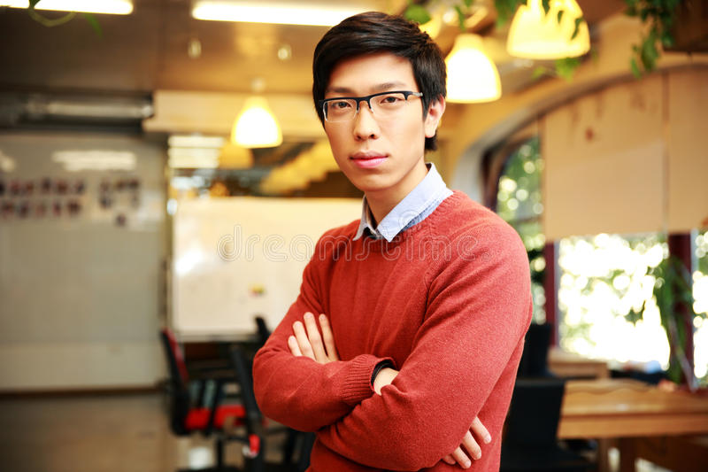Handsome asian man with arms folded standing. Portrait of a young handsome asian men with arms folded standing in office royalty free stock photos