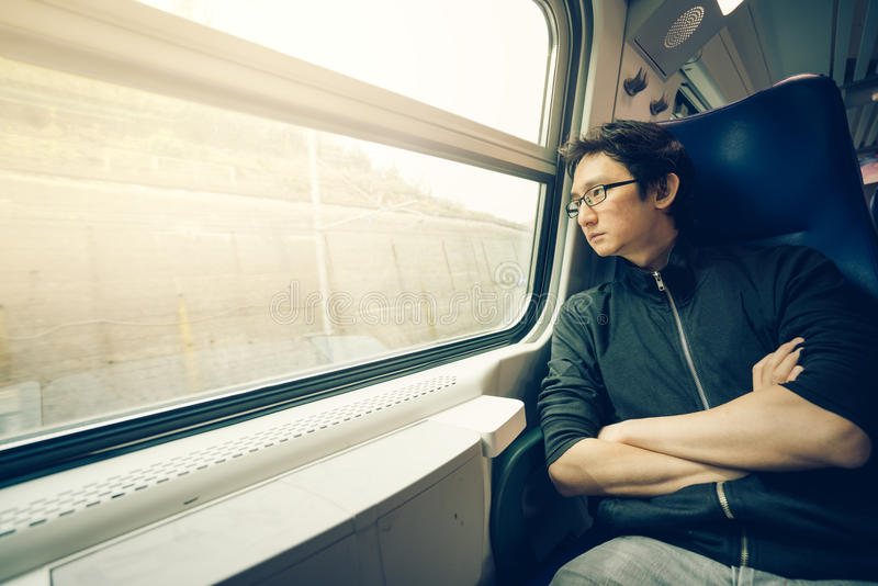 Handsome asian man looking through train window, warm light tone, with copy space stock photos