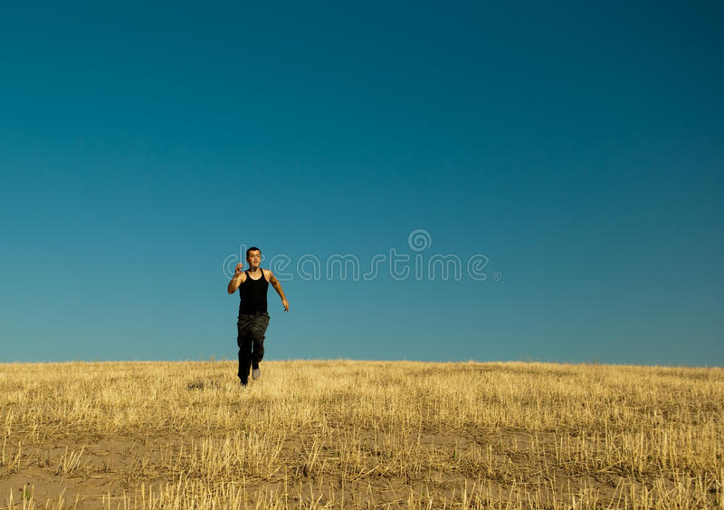 Handsome asian man running in the barley meadow in stock photo