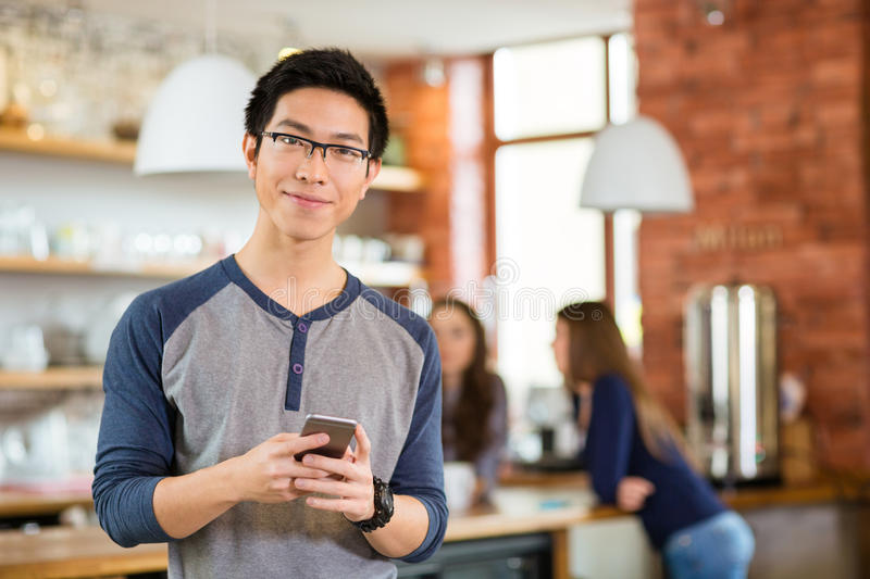 Handsome asian man standing in cafe and using mobile phone royalty free stock photography