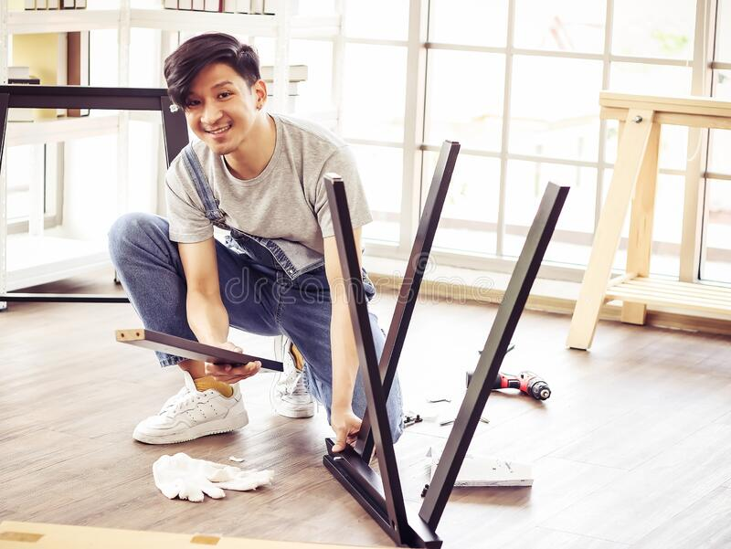 Handsome Asian man trying to assemble knock down furniture , smiling and looking at camera. Young and handsome Asian man trying to assemble knock down furniture royalty free stock photo