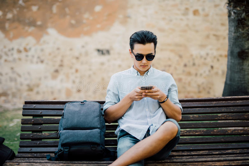 Handsome asian man typing message on his smart phone sitting on stock image