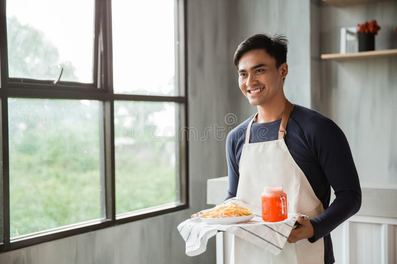 Handsome asian waiters wearing apron serving meal and beverage with smile royalty free stock images