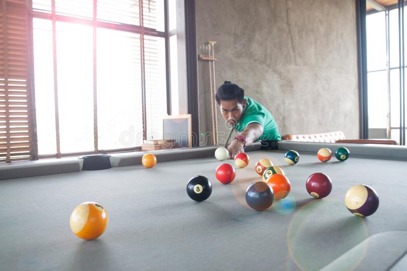 Handsome asian young man playing pool at home, Selective focus stock images