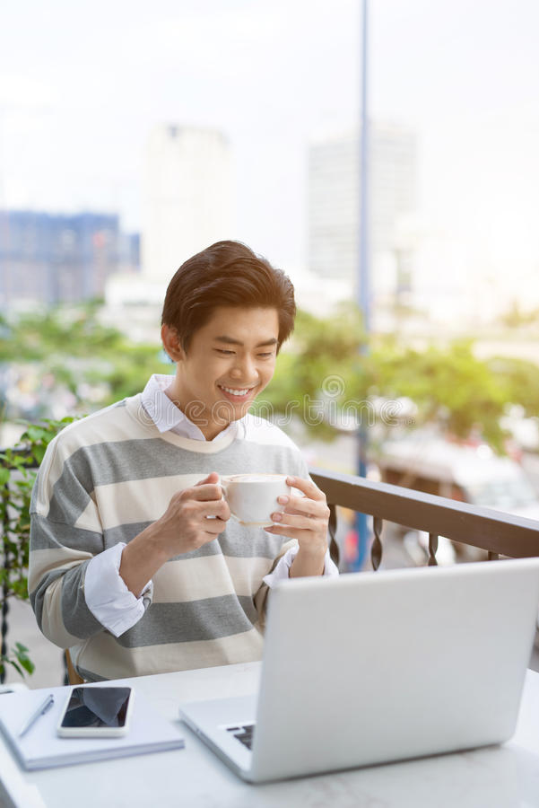 Handsome asian young man working on laptop and smiling while enjoying coffee in cafe stock photos