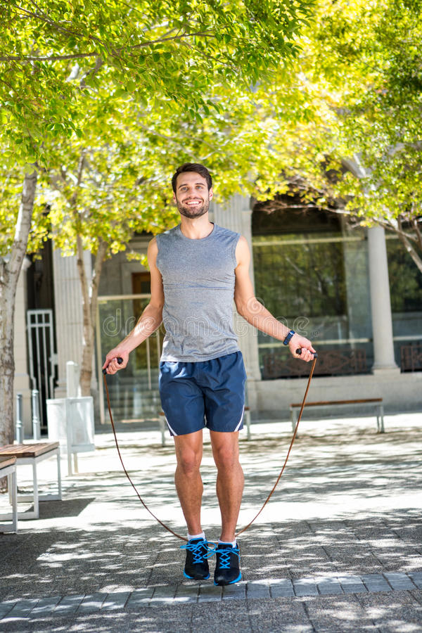 Handsome athlete doing jumping rope stock photo