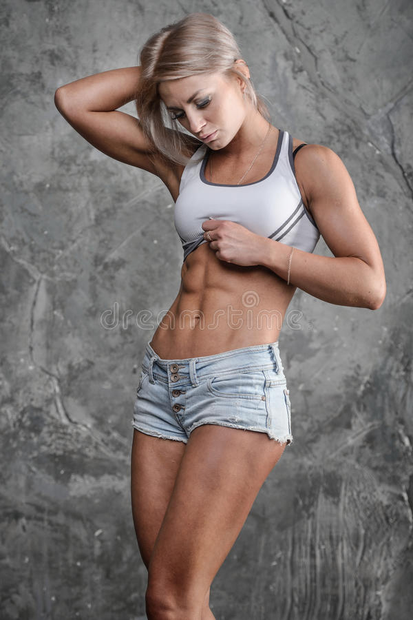 Handsome athletic fitness girl posing on a gray background in st stock photography